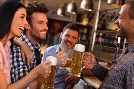 socializando: Feliz j�venes amigos bebiendo cerveza, divertirse en el pub, sonriendo. Foto de archivo