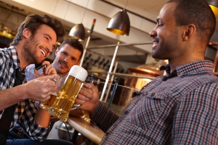 calling communication: Happy friends clinking with beer in pub, smiling.