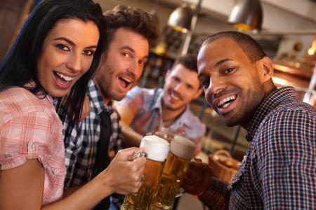 hombre tomando cerveza: Grupo de j�venes felices bebiendo cerveza, que se divierten en pub, ri�ndose. Foto de archivo