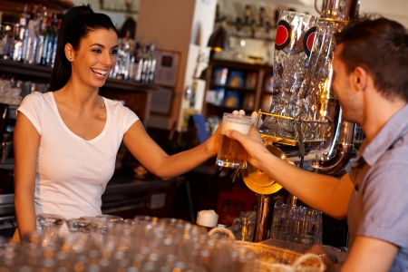 Attractive female bartender handing a glass of beer to customer at bar counter, laughing. photo