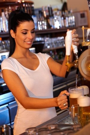 Portrait of attractive female bartender tapping beer in bar, smiling. photo