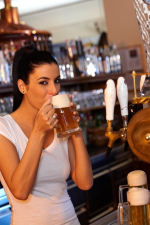 vertical bar: Attractive female bartender tasting freshly draught beer in bar