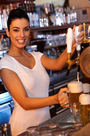 Portrait of attractive female bartender tapping beer in pub, looking at camera, smiling. Stock Photo
