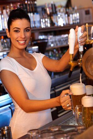 tapping: Ritratto di attraente barista femminile toccando birra in pub, guardando la fotocamera, sorridente.