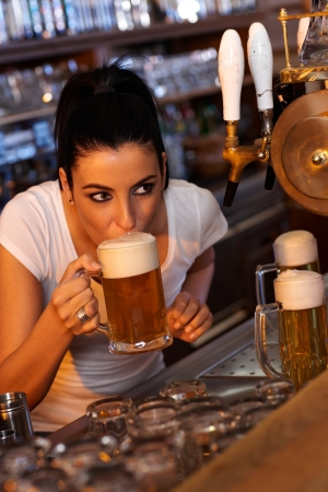pouring beer: Young female bartender tasting draft beer in bar Stock Photo
