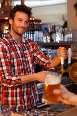 Portrait of young bartender tapping beer in pub, looking at customer, smiling. photo