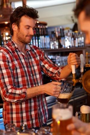 hombre tomando cerveza: Retrato de guapo camarero sirviendo cerveza en el pub, concentrándose.