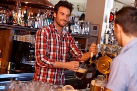 Retrato de joven camarero sirviendo cerveza en el pub, mirando al cliente con una sonrisa.