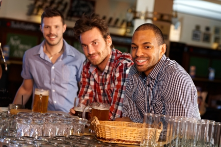 Portrait of young men drinking beer in pub, sitting at counter, smiling. photo