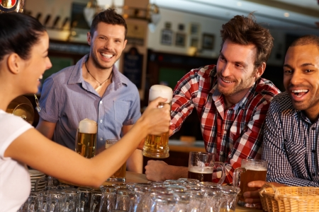 beer in bar: Happy friends drinking beer at counter in pub, chatting with female bartender, smiling. Stock Photo