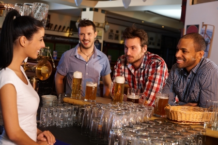 social drinking: Young men sitting at counter in pub, drinking beer and flirting with attractive bartender.