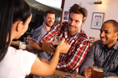 black man white woman: Happy young man getting a glass of beer from female bartender at counter, smiling.