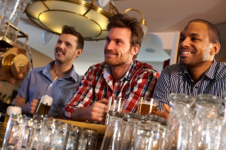 horizontal bar: Portrait of young men drinking beer at bar counter, smiling.