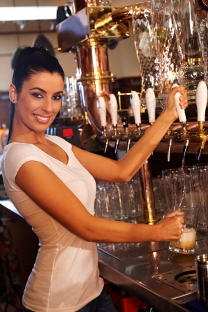 tapping: Portrait of attractive female bartender tapping mug of beer in pub, smiling. Stock Photo