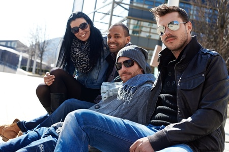 Group of trendy young people sitting outside of building, enjoying springtime sunshine photo