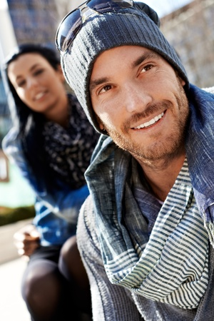 Outdoor portrait of handsome trendy man wearing designer scarf and hat photo
