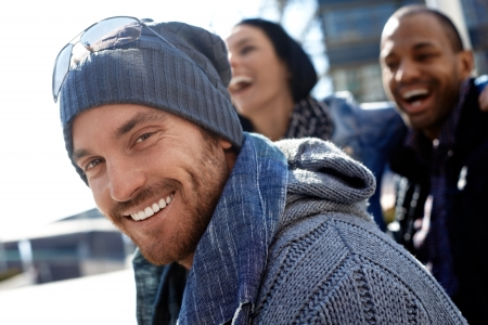 only 1 man: Outdoor portrait of happy young man wearing scarf and smiling at camera.