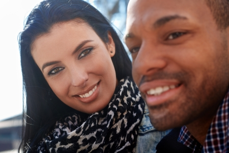 black woman white man: Outdoor portrait of young couple. Focus on woman looking to man, smiling. Stock Photo
