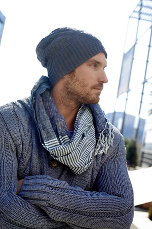 Outdoor portrait of trendy guy wearing scarf and hat, arms crossed. Stock Photo
