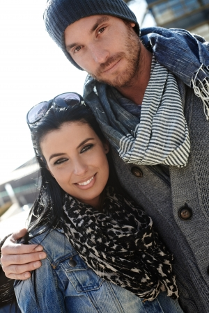 winter day: Outdoor portrait of trendy young couple wearing scarf.