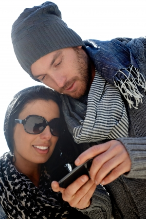 warm clothes: Closeup portrait of trendy young couple using mobile, looking at screen, smiling.