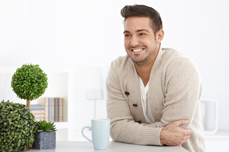 bristly: Happy young man smiling at home, looking away. Stock Photo
