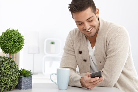 Happy young man using mobile phone at home, smiling. Stock Photo - 15032845
