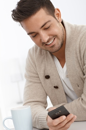 bristly: Portrait of young man using mobilephone, smiling.