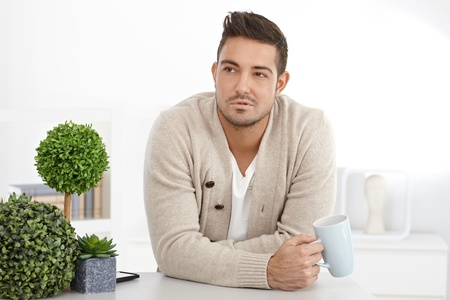 Portrait of disappointed young man at home drinking tea. Stock Photo - 15032869