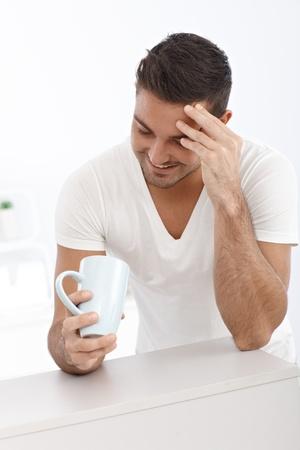 Happy young man looking at tea mug, smiling. photo