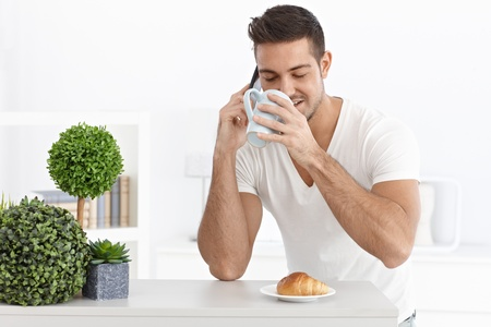 Morning portrait of young man with mobile and tea mug. Stock Photo - 15032830