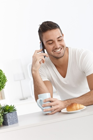 Happy man having breakfast, talking on mobile phone. photo