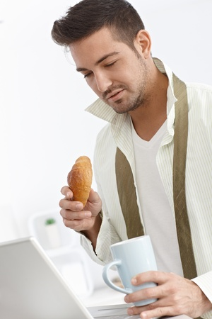 bristly: Young businessman having breakfast, using laptop computer in the morning.