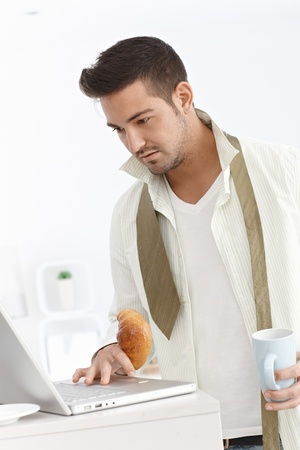 Young businessman using laptop computer, having breakfast at home in the morning. Stock Photo - 15032827