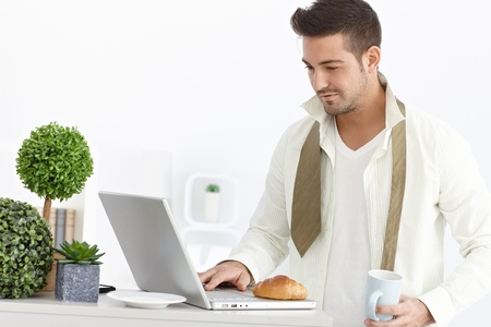 Young businessman having breakfast, checking mail on computer in the morning. Stock Photo - 15032824