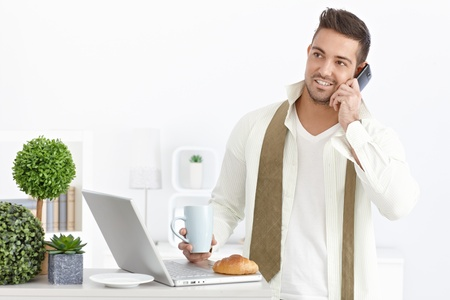 young unshaven: Busy businessman having breakfast at home, using computer, talking on mobile phone.