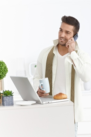 Young businessman talking on mobile, having breakfast, using laptop computer at home in the morning. photo