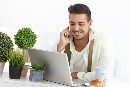 Young businessman having breakfast at home, using laptop and mobile phone. Stock Photo - 15032852