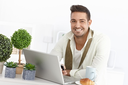 Happy young businessman using laptop and mobile during breakfast. Stock Photo - 15032843