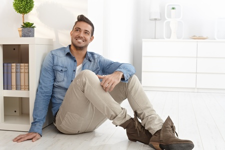Happy young man daydreaming at home, sitting on floor. Stock Photo - 15032918