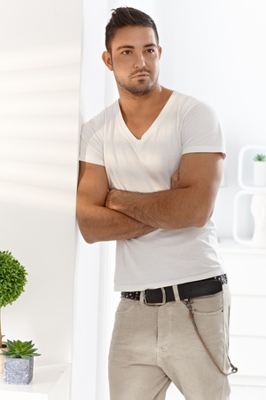 Casual young man standing arms crossed at home, leaning to wall. photo