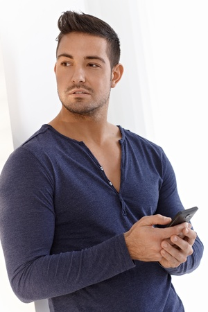 Athletic young man using mobilephone, texting. photo