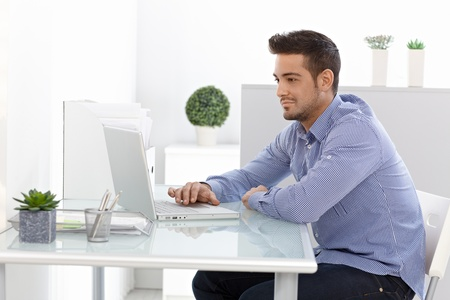 home office: Young man using laptop computer, working at home.