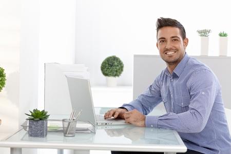 Happy businessman working on laptop computer, sitting at desk.