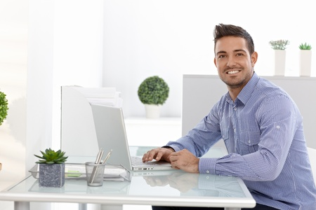 Happy businessman working on laptop computer, sitting at desk. photo