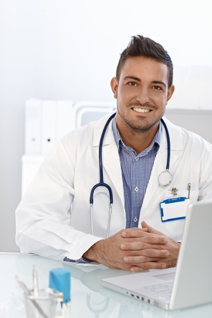 Happy young male doctor sitting at desk, working on computer. photo