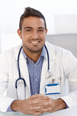 doctors smiling: Portrait of young male doctor smiling, sitting at desk.