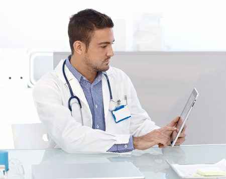 Young male doctor using tablet computer, sitting at desk in doctors room. photo