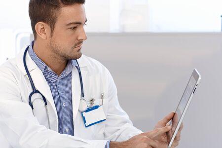 visage profil: Jeune médecin de sexe masculin en utilisant l'ordinateur tablette, vue de côté. Banque d'images