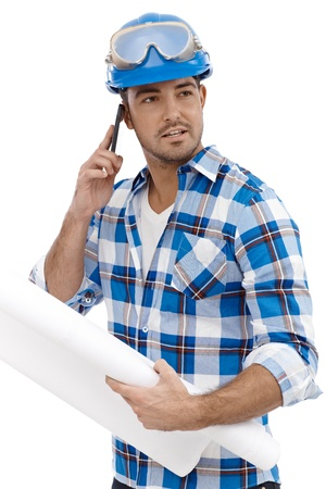 Young engineer working in hardhat, talking on mobile phone. Stock Photo - 15032931